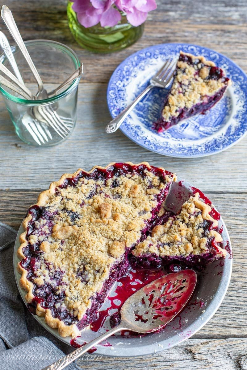 A sliced blueberry pie with blueberry juices all over the pan