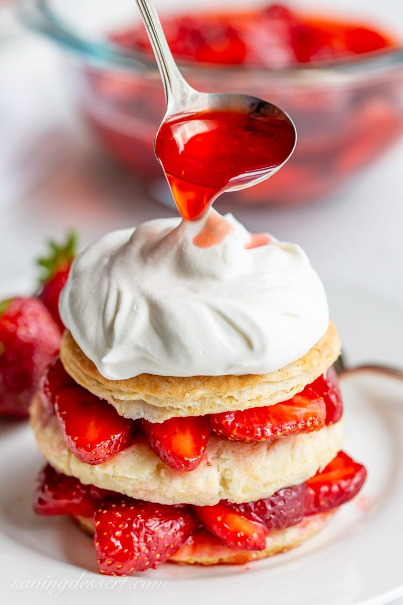 Strawberry Shortcake Scones stacked with fresh strawberries, whipped cream and strawberry syrup