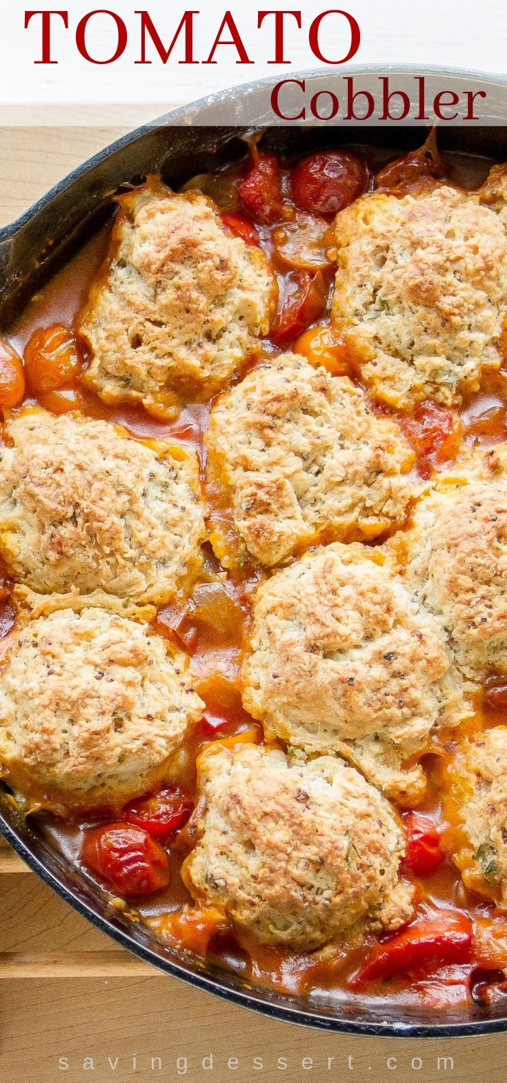A skillet with savory tomato cobbler topped with herbed biscuits