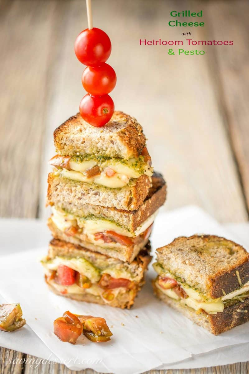 A stacked grilled cheese sandwich with pesto and tomatoes