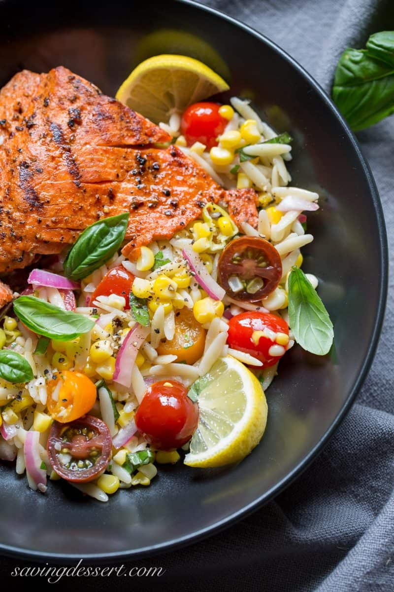 A bowl of grilled salmon with an orzo corn salad and fresh herbs