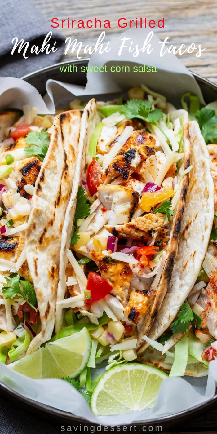 Sriracha Grilled Mahi Mahi Fish Tacos with Sweet Corn Salsa - spicy, flaky, mild Mahi Mahi piled on grilled tortillas with cabbage, cheese, and sour cream! #savingroomfordessert #fishtacos #tacotuesday #taco #sriracha #grilleddtacos #sweetcornsalsa #cornsalsa