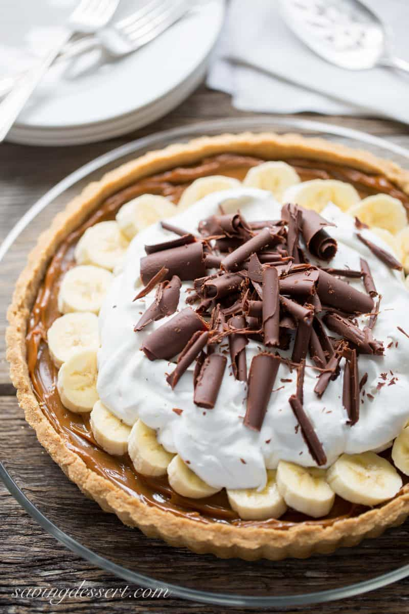 A pretty banoffee pie with silky caramel, fresh sliced bananas, whipped cream and chocolate curls