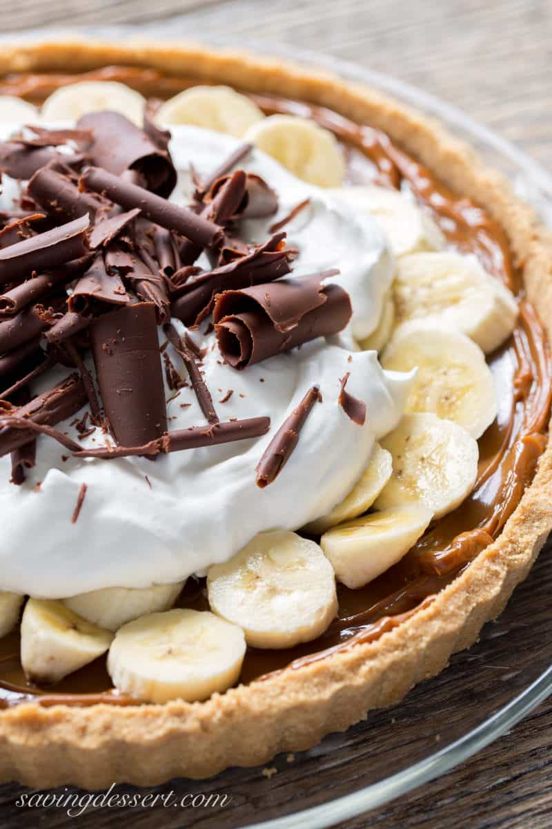 A banoffee pie with a cookie crust, smooth caramel filling, topped with sliced bananas, whipped cream and chocolate curls