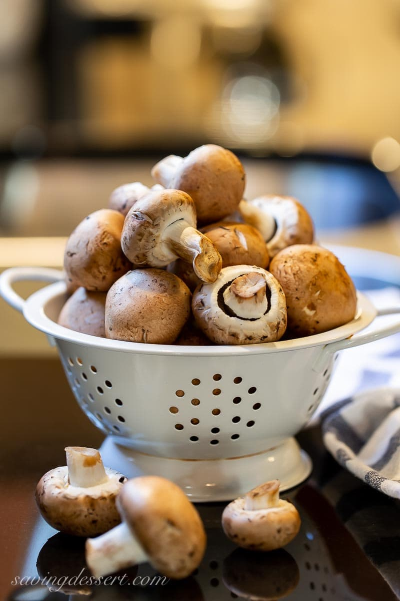 A colander filled with brown mushrooms