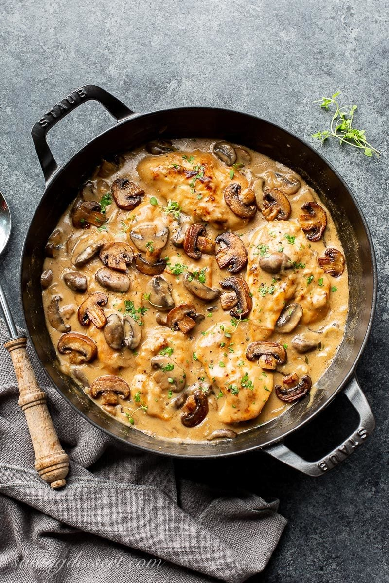 A skillet with chicken and mushrooms with fresh thyme