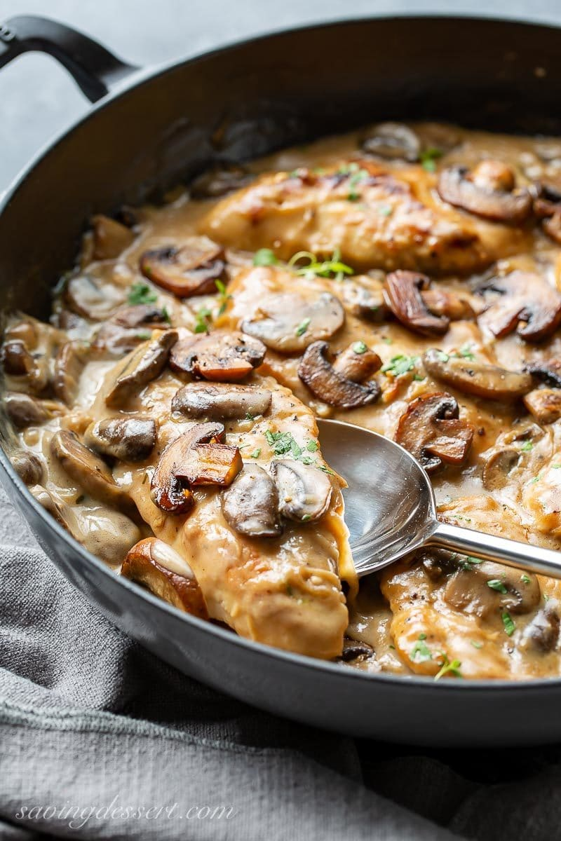 A skillet filled with chicken cutlets in a mushroom wine sauce