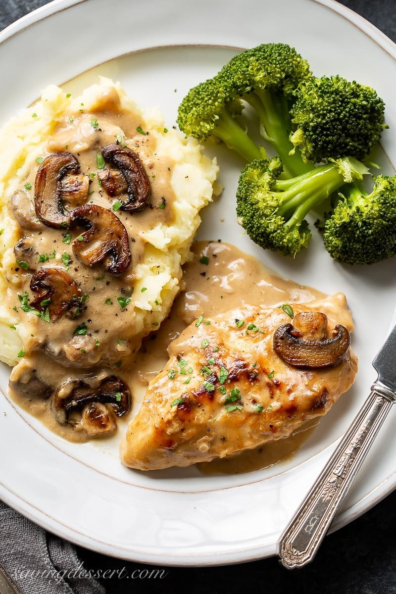 A plate with chicken in mushroom wine sauce with broccoli and mashed potatoes