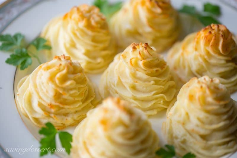 Duchess Potatoes ~ delicious mashed potatoes piped into swirls, drizzled with butter and baked to golden, puffy perfection. So easy and pretty too! www.savingdessert.com #savingroomfordessert #potatoes #duchess #sidedish
