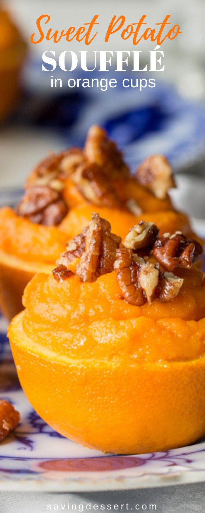 A light fluffy sweet potato filling flavored with fresh squeezed orange juice, topped with cinnamon sugar pecans and baked in an orange cup - a lovely side dish for your holiday buffet table! #orangesweetpotatoes #sweetpotatoes #sweetpotatosouffle #holidaysidedish #soufflé #potatoes #thanksgiving #christmas
