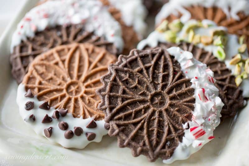 Chocolate Pizzelles dipped in white chocolate with peppermint, walnuts, chocolate chips, coconut and pistachios