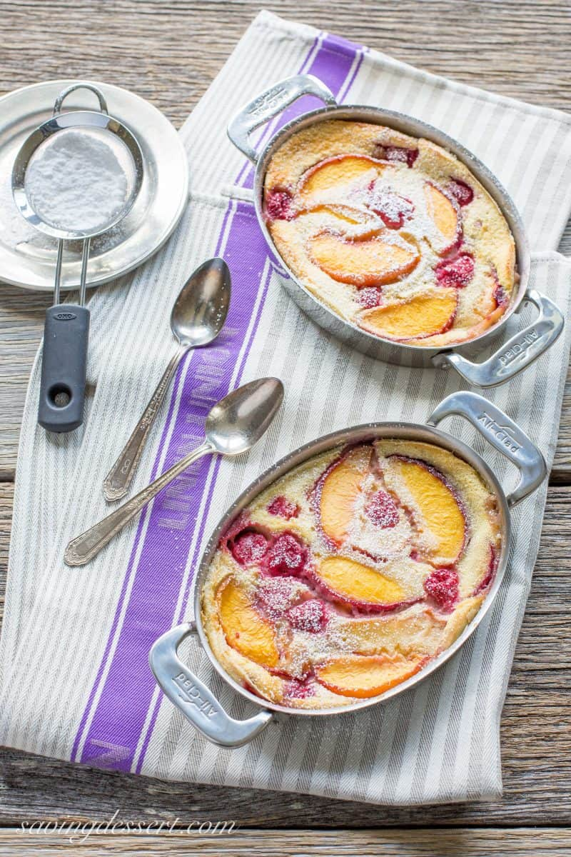 peach and raspberry clafoutis in two small casserole pans