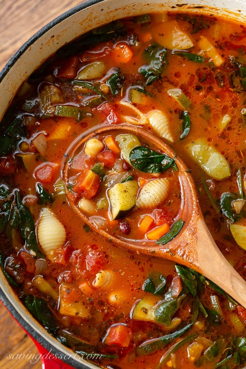 A pot of vegetable soup with shell shaped pasta in a tomato broth