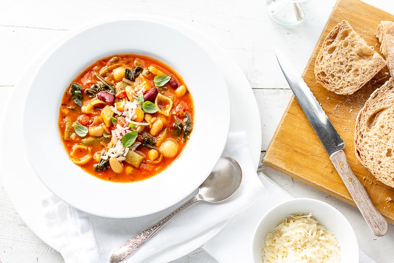 A bowl of easy Minestrone Soup with grated Parmesan and fresh bread