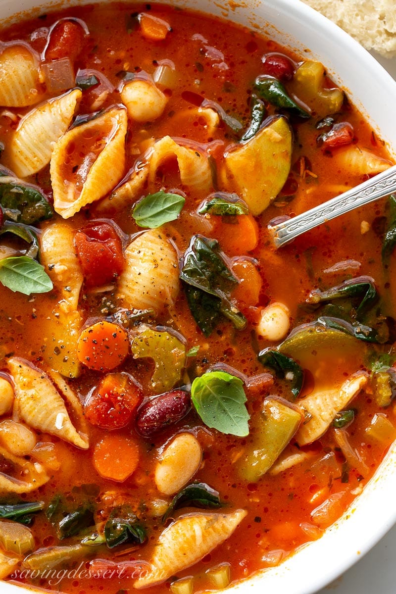 A hearty bowl of vegetable soup with shell shaped pasta, basil leaves and spinach