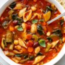 A close up of a bowl of Minestrone Soup with spinach and fresh basil leaves