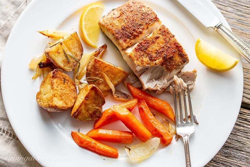 A plate with a piece of baked fish, carrots and potatoes