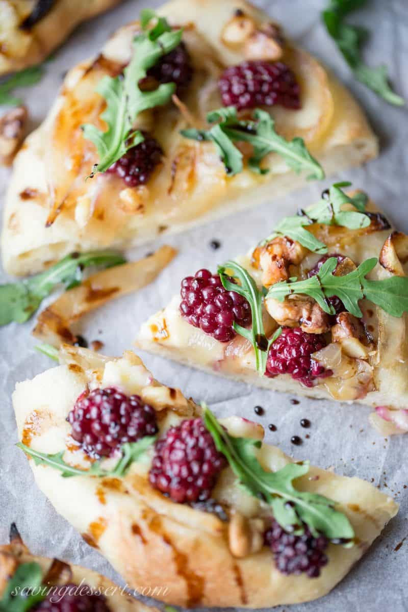 Blackberries and brie cheese made into a mini pizza with caramelized onions, arugula and a drizzle of balsamic