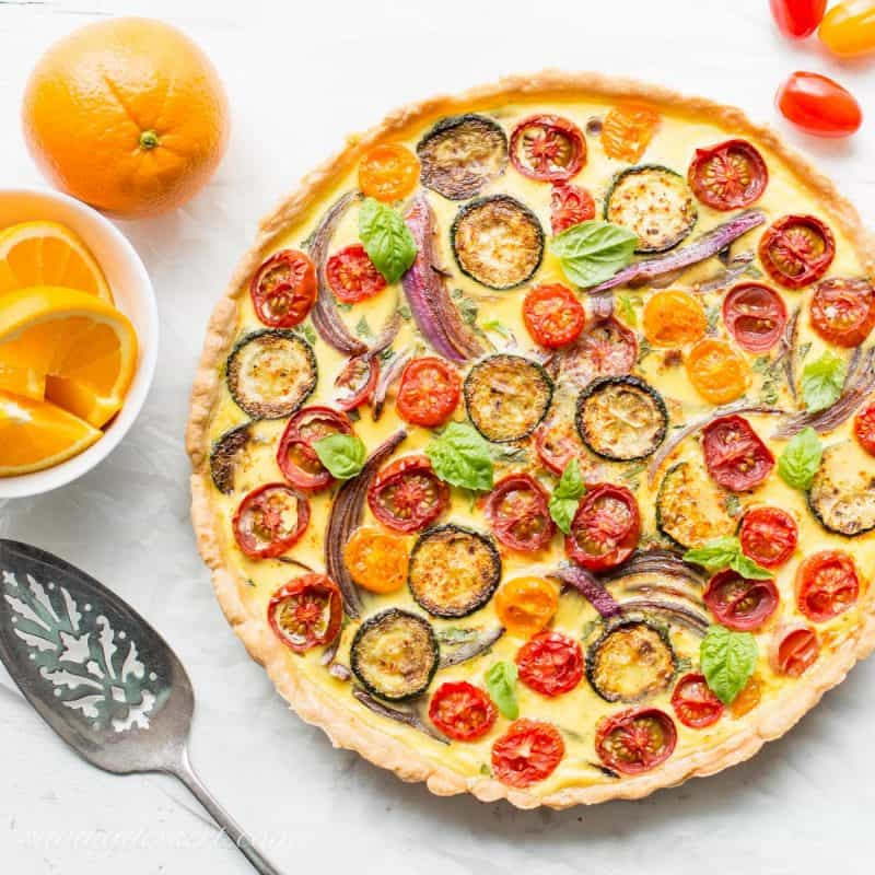 A Farmers Market Quiche loaded with fresh tomatoes, herbs, onions and zucchini. Served with fresh sliced oranges