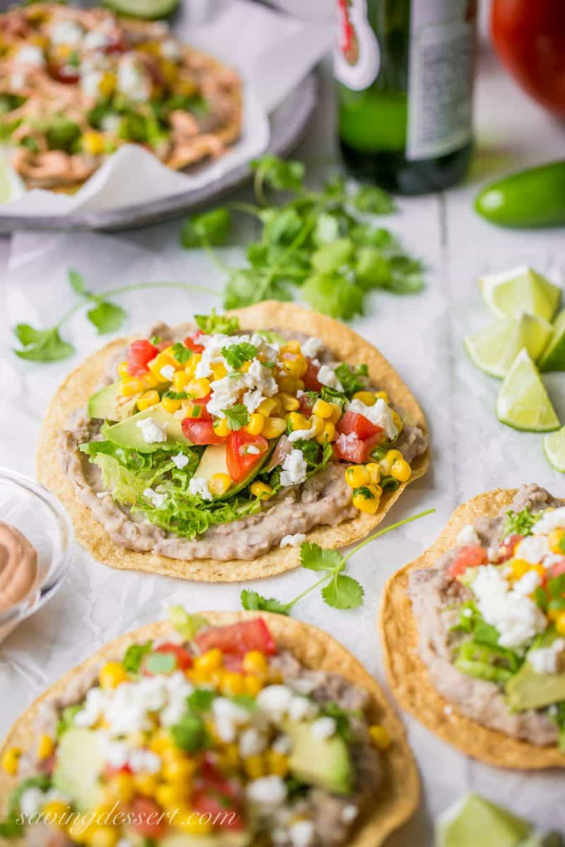 Homemade refried beans on tostadas, topped with tomatoes, cheese, avocado and corn
