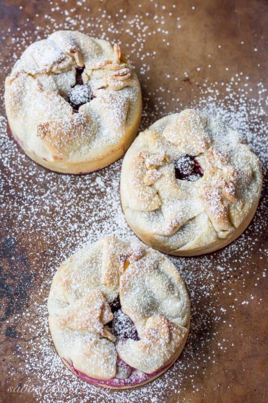 Mini deep dish berry pies on a baking pan