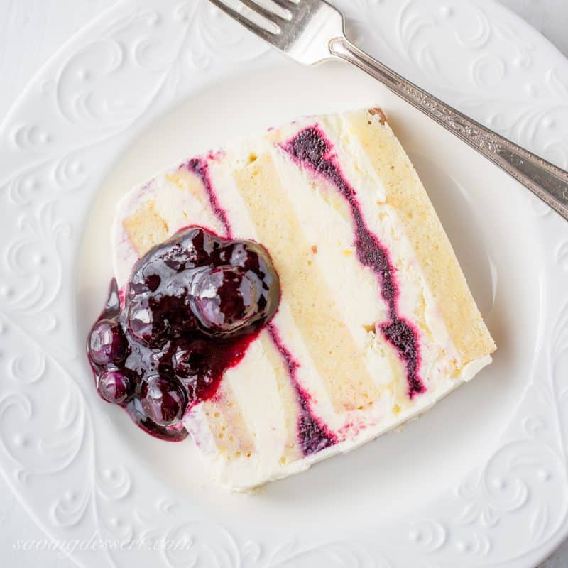 A slice of blueberry lemon icebox cake with blueberry sauce on top