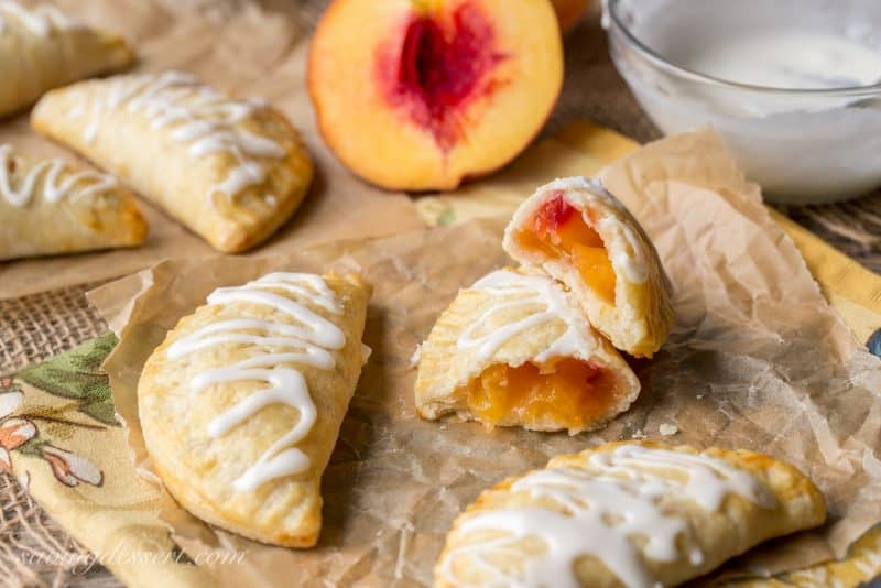 A few hand pies on parchment paper with one broken in half revealing a pretty peach filling