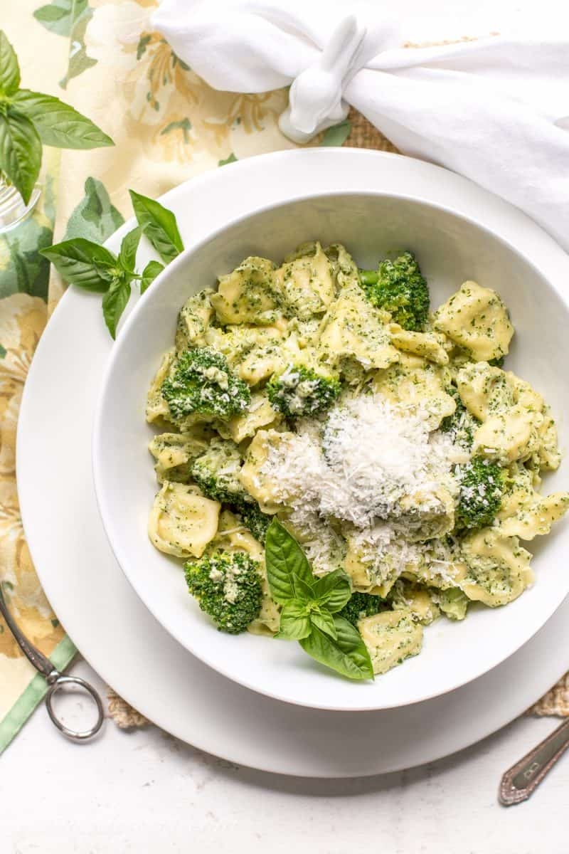 A bowl of tortellini pasta with broccoli, fresh basil and a pesto cream sauce