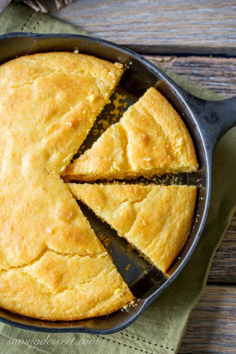 A cast iron skillet with a cake of sliced cornbread