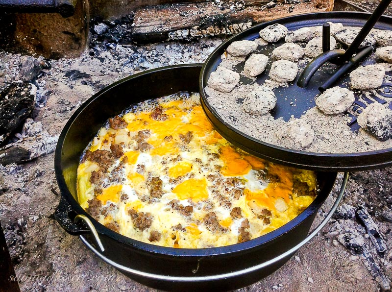 A cast iron Dutch oven over an open fire with a sausage casserole