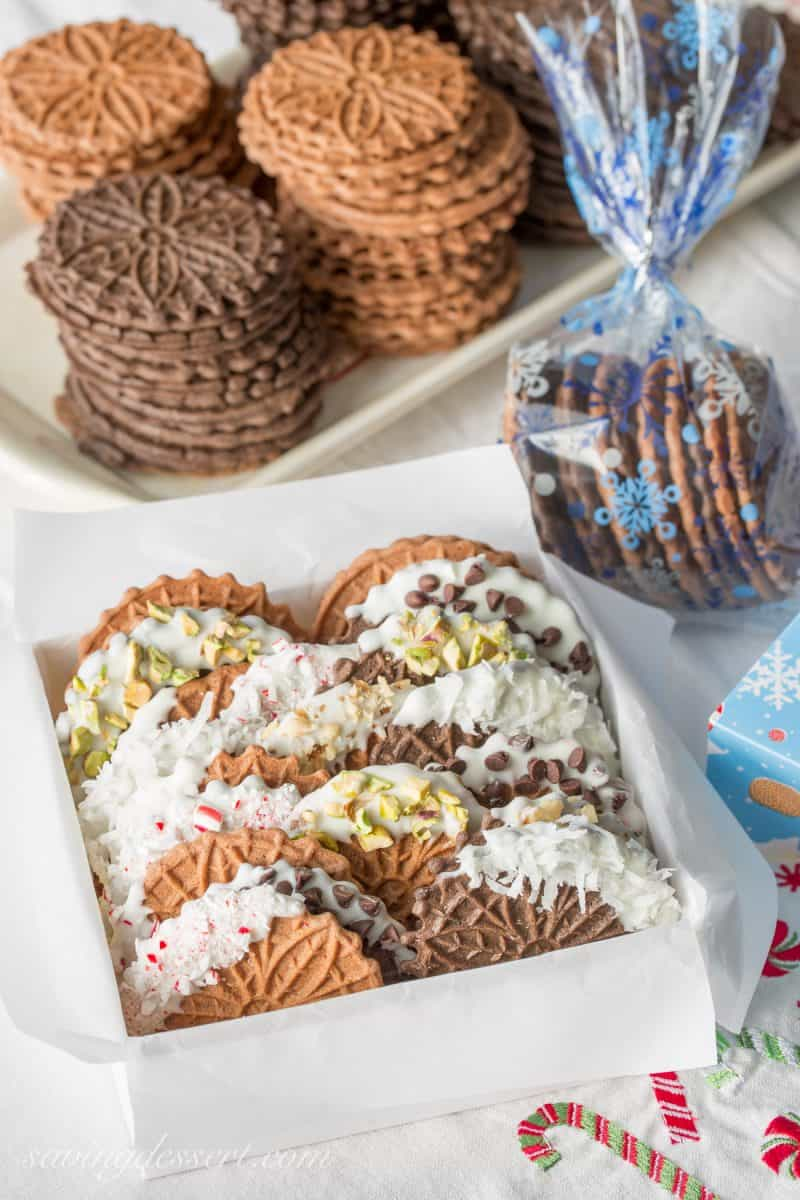 Chocolate Pizzelles dipped in white chocolate and decorated with coconut, crushed peppermint, nuts and mini chocolate chips