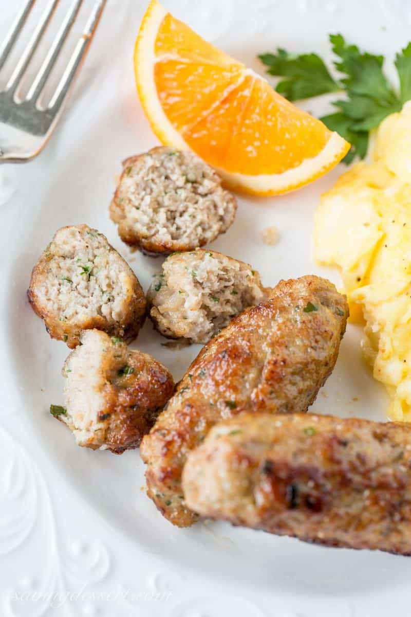 Homemade breakfast sausage on a plate with eggs and an orange slice