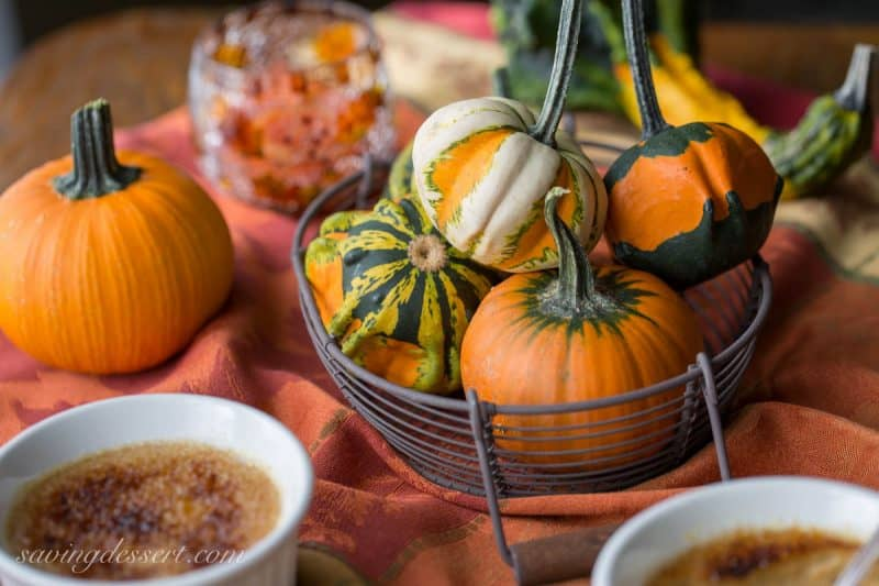 Mini pumpkins and gourds in a basket on a table with pumpkin creme brûlée