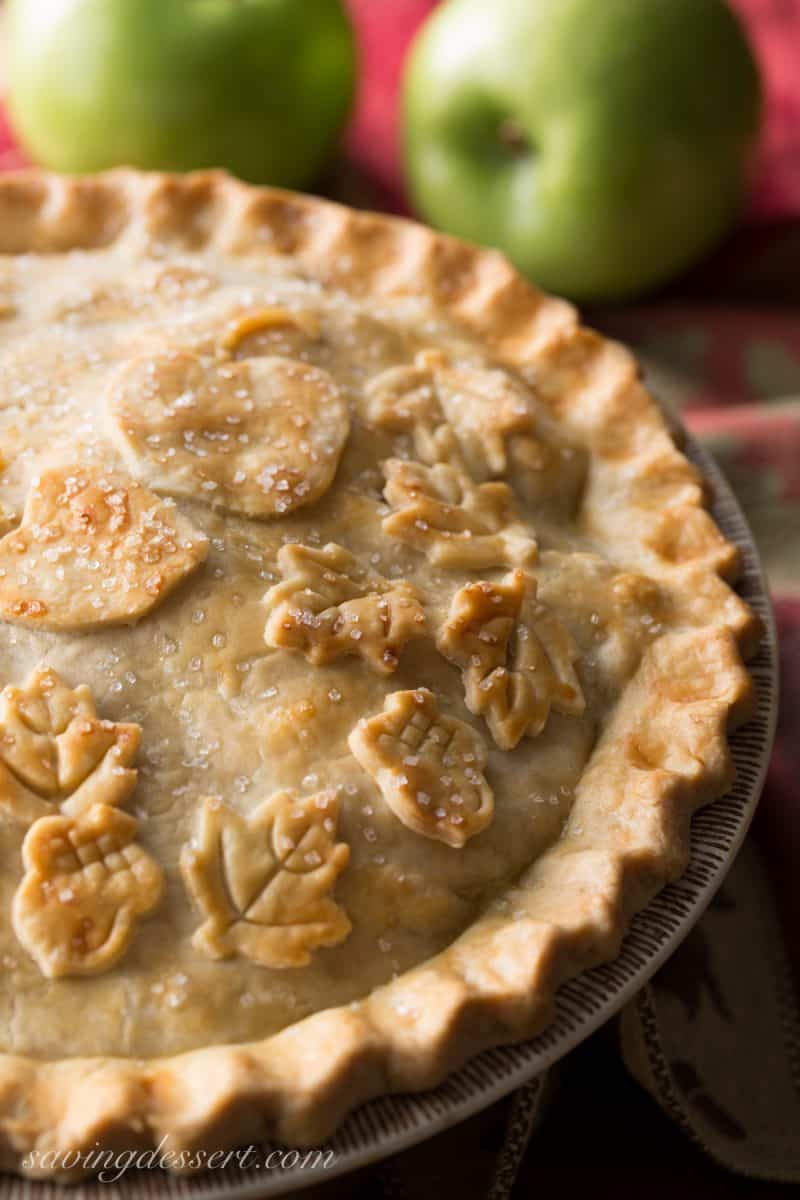 A classic baked apple pie decorated with acorns, leaves and apples cut out of pastry.