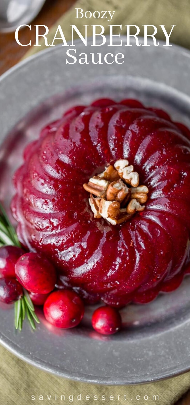 A molded ring of boozy cranberry sauce with fresh cranberry garnish and pecans.