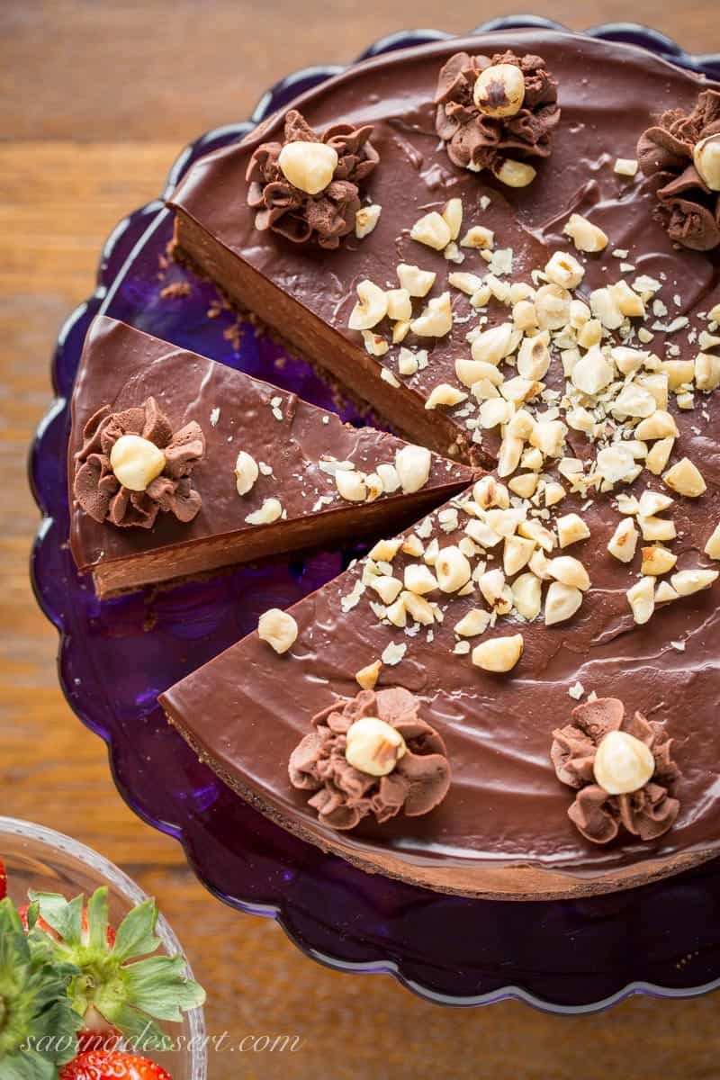 An overhead view of a Chocolate Hazelnut Mousse Cake topped with hazelnuts and chocolate ganache