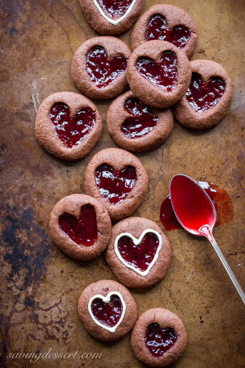 Chocolate Raspberry Thumbprint Cookies - who can resist the classic combination of raspberries and chocolate?! This little chocolate cookie boasts plenty of chocolate flavor and a fun little heart shaped thumbprint filled with seedless raspberry jam. An easy and delicious cookie with a Valentine's Day theme for your sweetie! www.savingdessert.com