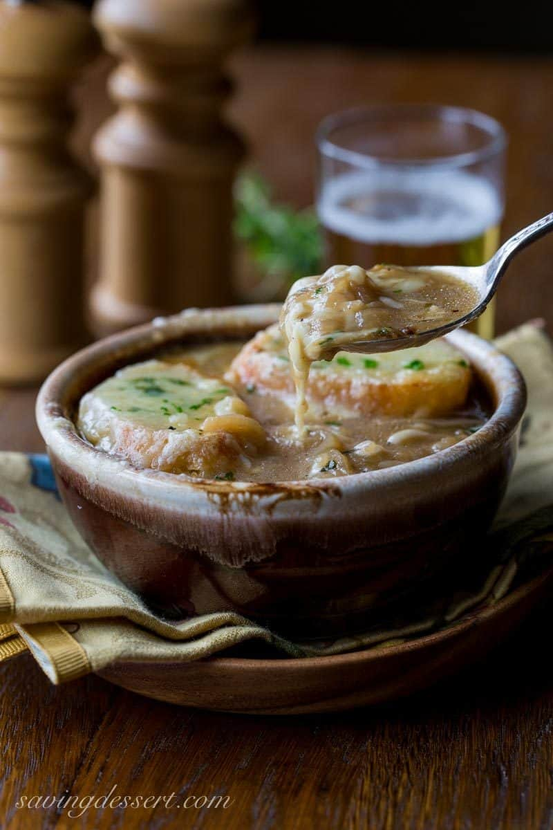 French Onion Soup loaded with sweet caramelized onions, fresh thyme, beef stock and a big splash of pale lager, then topped with toasted garlic croutons and plenty of strong Gruyère cheese. Oh my this is good! www.savingdessert.com