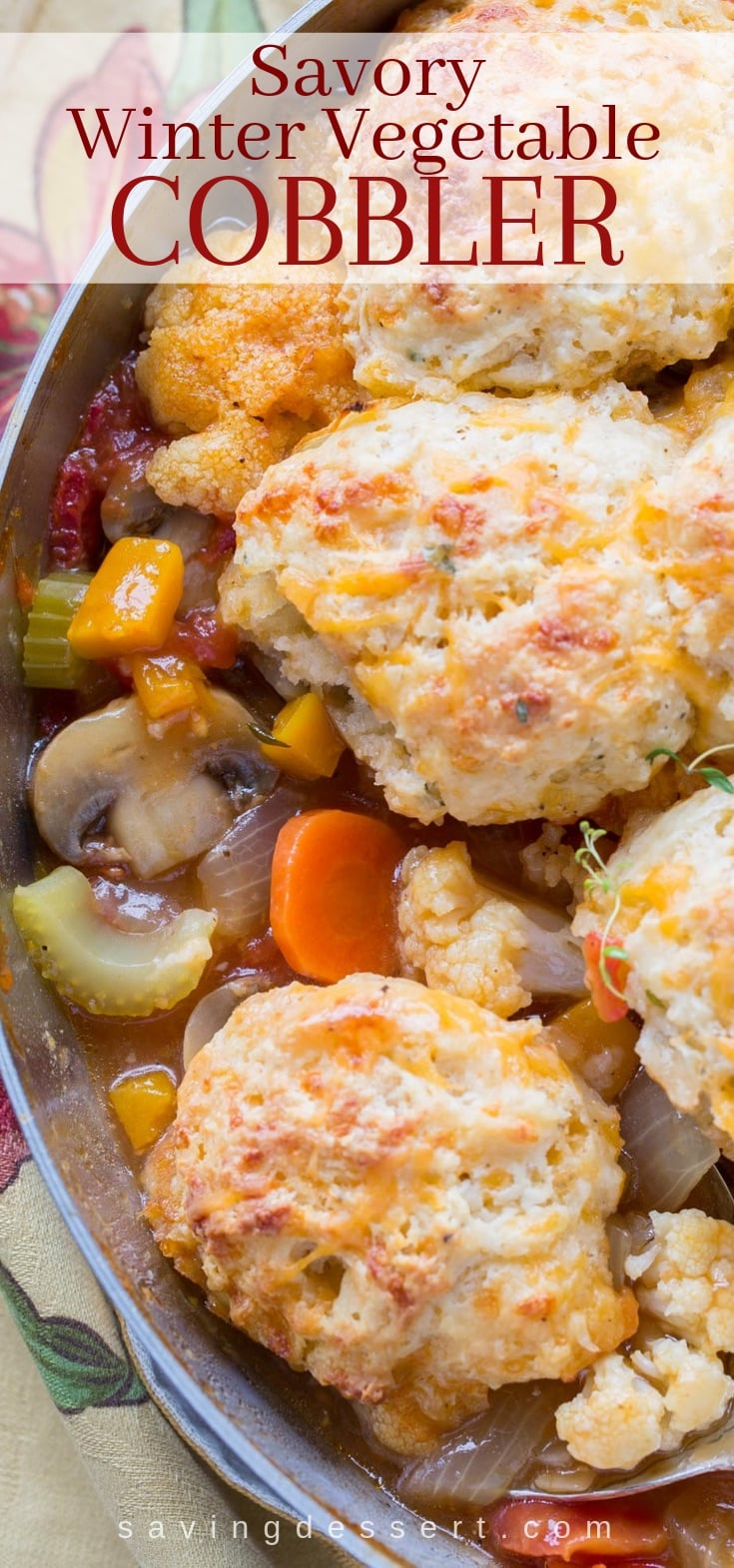 A skillet filled with a savory winter vegetable cobbler topped with herbed cheese biscuits