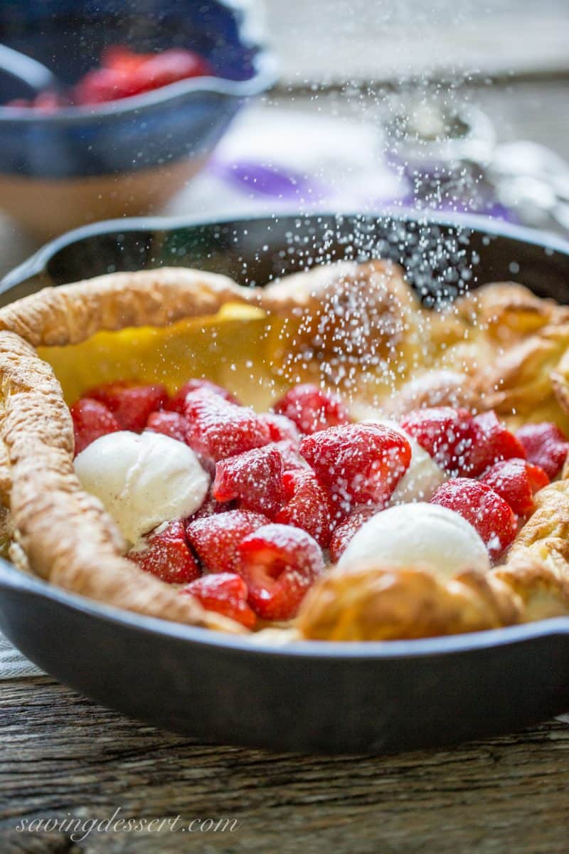 Strawberry Dutch Baby - this Dutch Baby, or German Pancake, is topped with Grand Marnier soaked Strawberries and Vanilla Bean Ice Cream – a super easy and impressive dessert! www.savingdessert.com