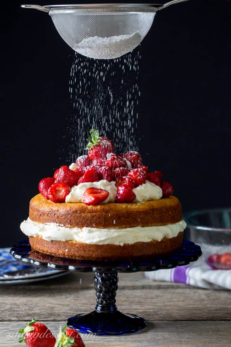 A simple lemon cake filled with whipped cream and topped with strawberries