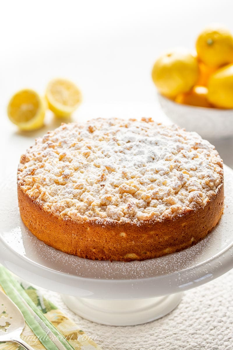 Lemon Crumble Breakfast Cake on a cake stand with lemons