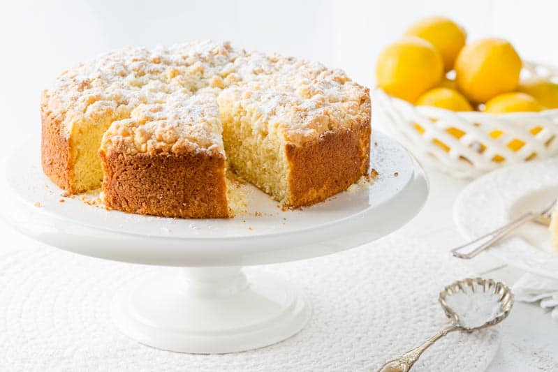 A lemon crumble cake sprinkled with powdered sugar on a cake stand