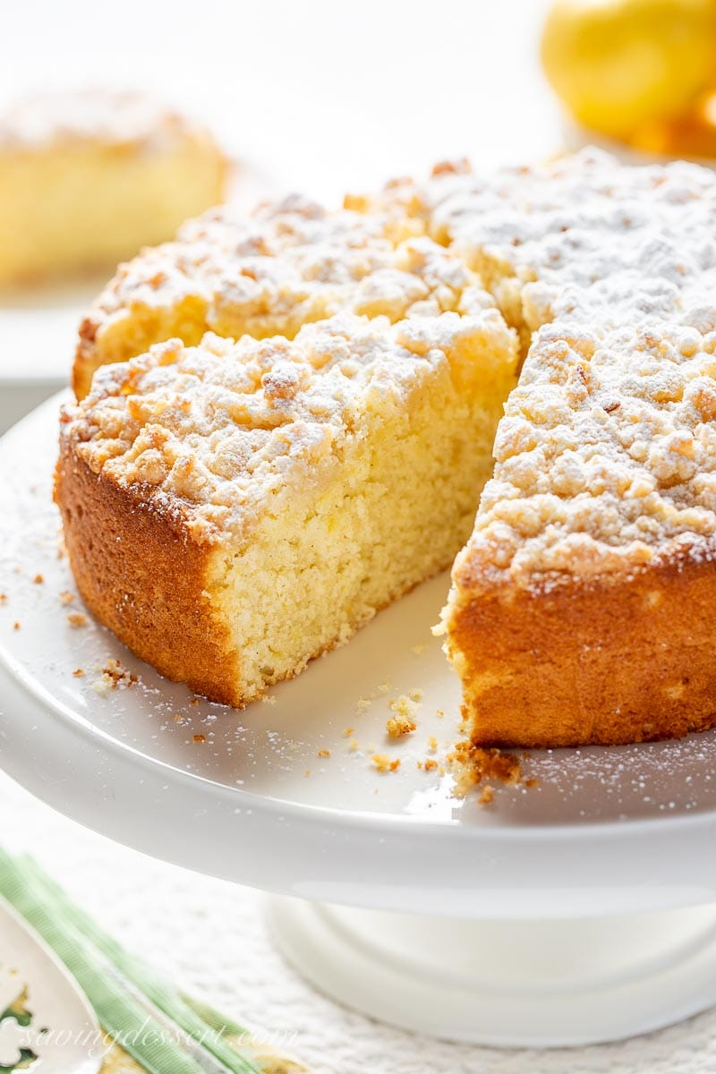 A sliced lemon cake with a crumble topping on a cake stand