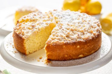 A single layer lemon cake with a sweet crumbled topping