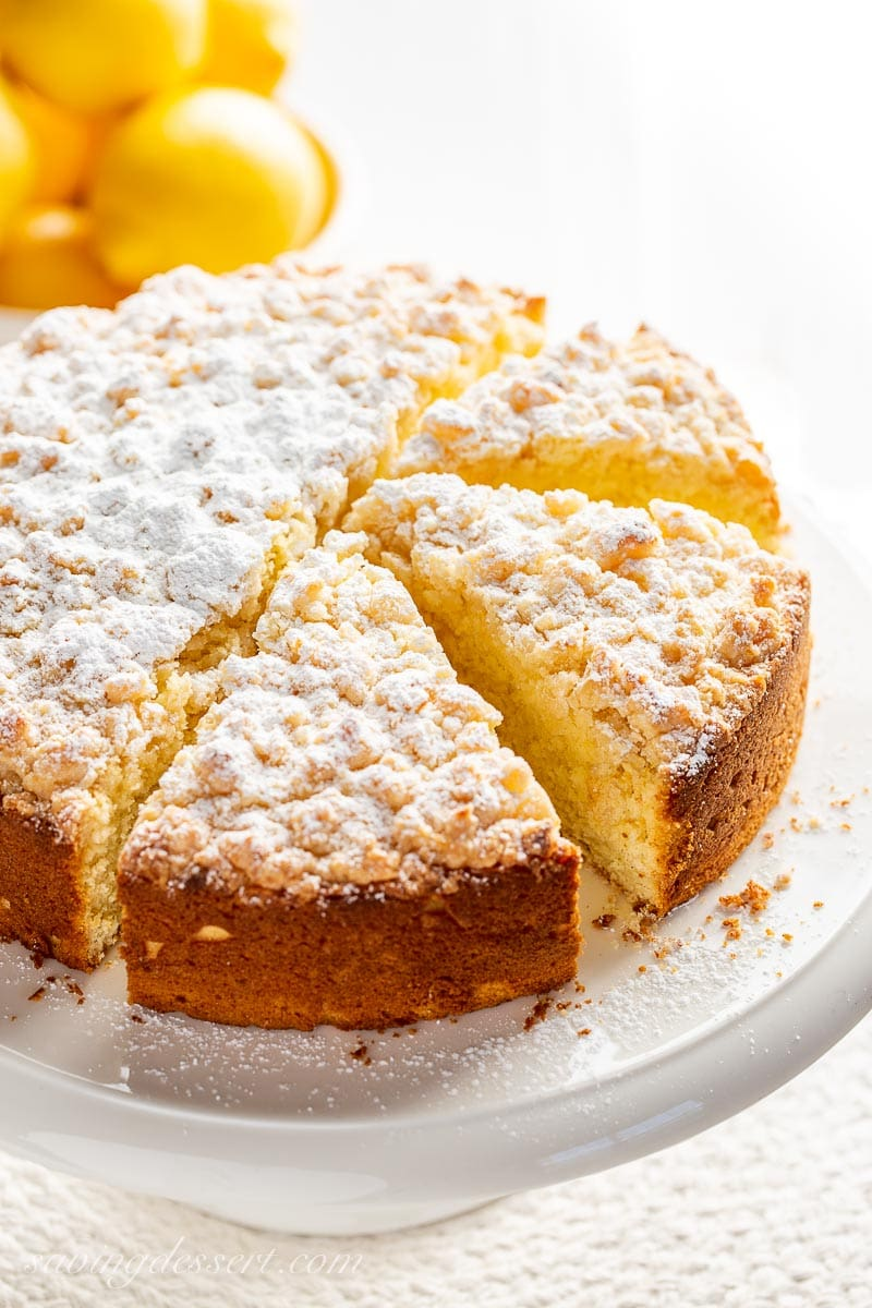 An overhead photo of a sliced lemon cake on a cake stand