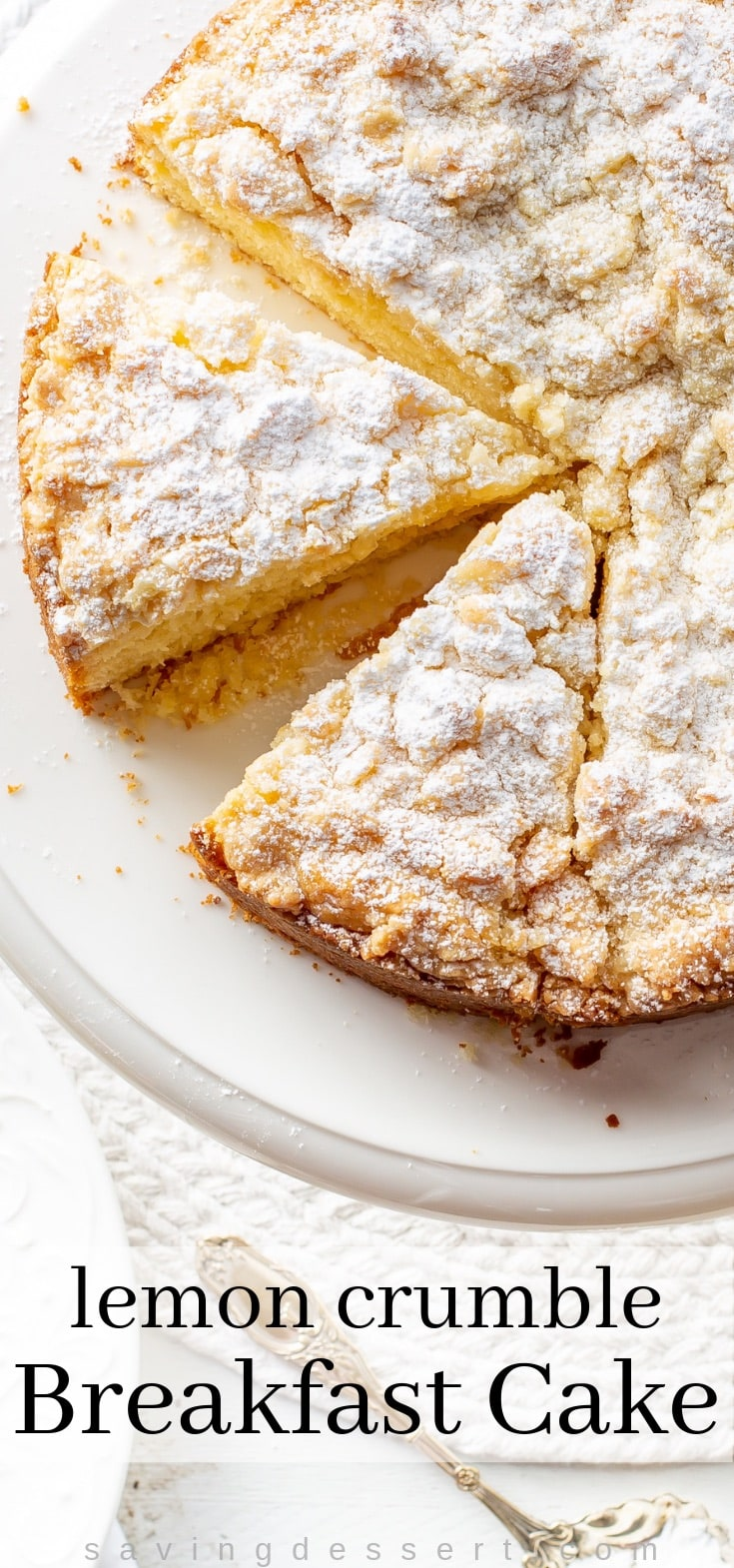 A cake plate with a sliced lemon crumble cake dusted with powdered sugar