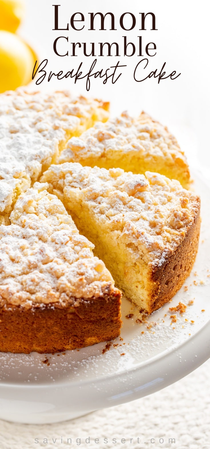 Lemon Crumble Breakfast Cake dusted with powdered sugar on a cake stand