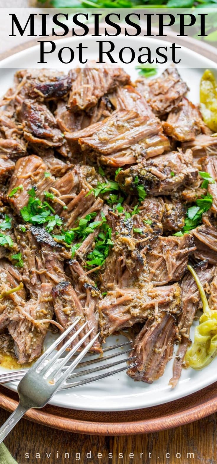A platter with shredded Mississippi Pot Roast with peppers garnished with parsley