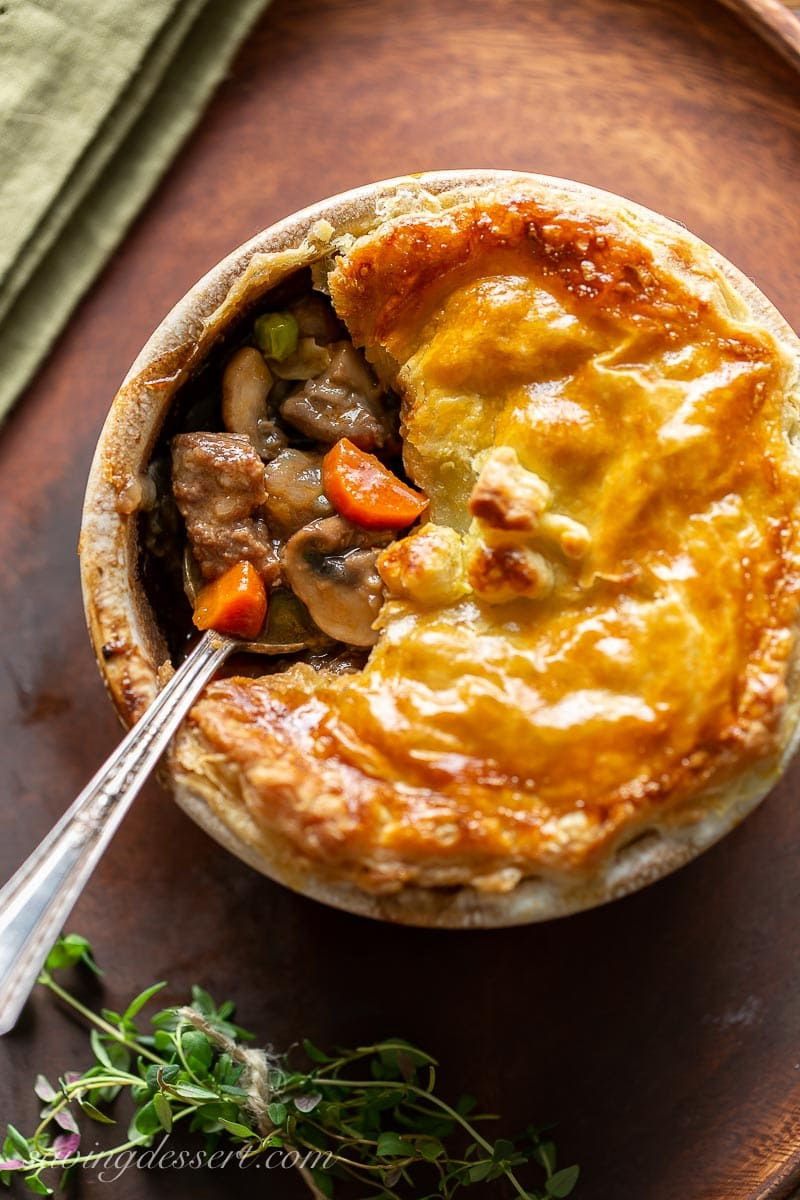 A beef pie with carrots and peas topped with golden brown puff pastry
